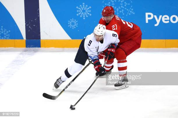 Brian O'Neill of the United States handles the puck against Sergei Kalinin of Olympic Athlete from Russia during the Men's Ice Hockey Preliminary...