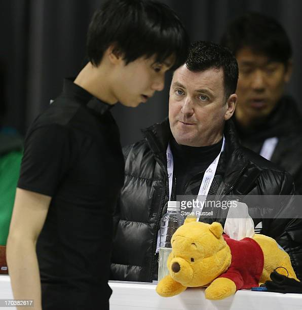Brian Orser and Winnie the Pooh look on as their skater Japan's Yuzuru Hanyu practices in preparation for the ISU World Figure Skating Championships...