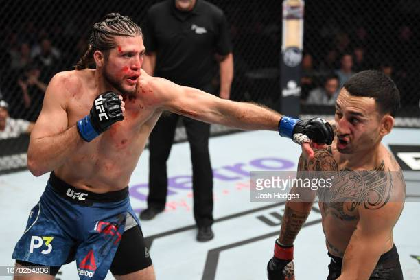 Brian Ortega punches Max Holloway in their UFC featherweight championship fight during the UFC 231 event at Scotiabank Arena on December 8, 2018 in...
