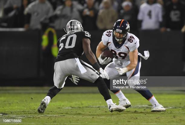 Brian Parker of the Denver Broncos catches a pass and looks to put a move on Nicholas Morrow of the Oakland Raiders during the first half of an NFL...