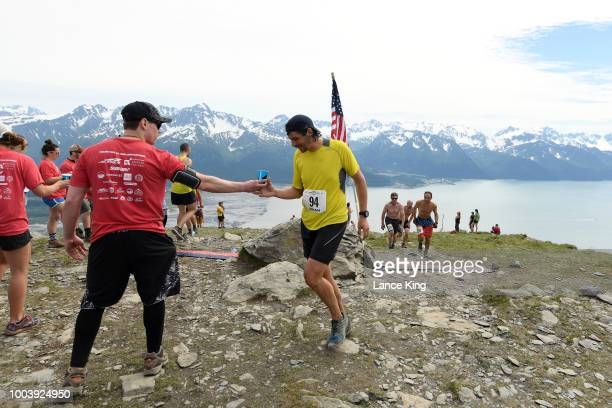 Brian Pautzke gets a drink as he passes the top of Mount Marathon during the Men's Division of the 91st Running of the Mount Marathon Race on July 4...