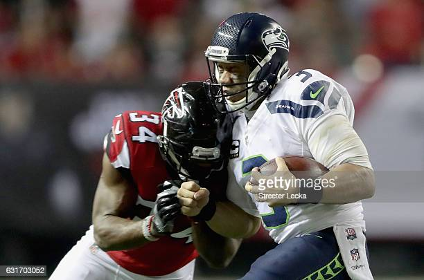 Brian Poole of the Atlanta Falcons hits Russell Wilson of the Seattle Seahawks during their game at the Georgia Dome on January 14 2017 in Atlanta...
