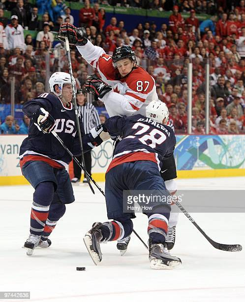 Brian Rafalski and Ryan Suter of USA play the body against Sidney Crosby of Canada in the first overtime during the ice hockey men's gold medal game...