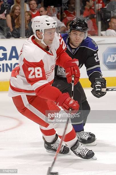 Brian Rafalski of the Detroit Red Wings handles the puck as Alexander Frolov of the Los Angeles Kings defends during their game on October 14 2007 at...