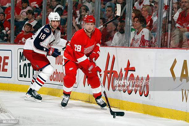 Brian Rafalski of the Detroit Red Wings skates with the puck against RJ Umberger of the Columbus Blue Jackets during Game One of the Western...