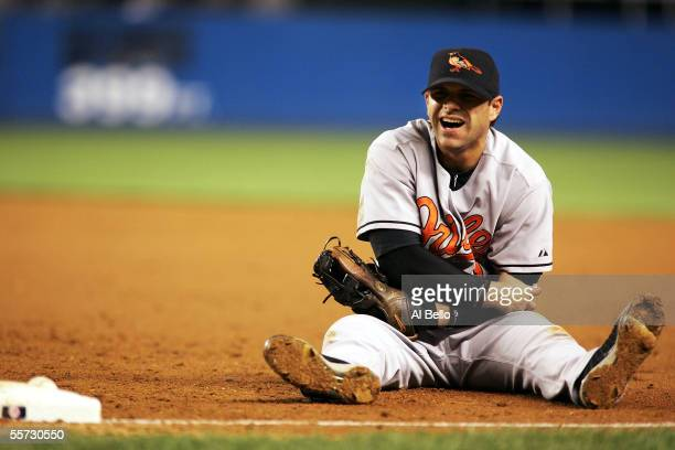 Brian Roberts of the Baltimore Orioles holds his arm after a collision at first base attempting to tag out Bubba Crosby of the New York Yankees on...