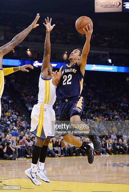 Brian Roberts of the New Orleans Pelicans goes up for a layup over Toney Douglas of the Golden State Warriors at ORACLE Arena on December 17 2013 in...