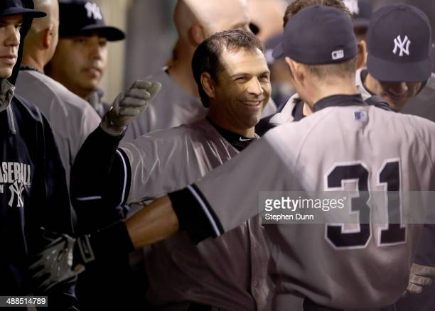 Brian Roberts of the New York Yankees is greeted in the dugout by Ichiro Suzuki after hitting a solo home run in the ninth inning for the evnetual...