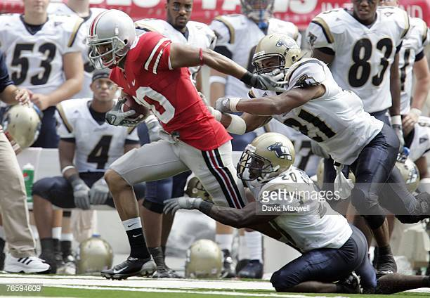 Brian Robiskie of the Ohio State Buckeyes is forced out of bounds by Reggie Corner and Andrew Johnson of the Akron Zips in front of the Akron bench...