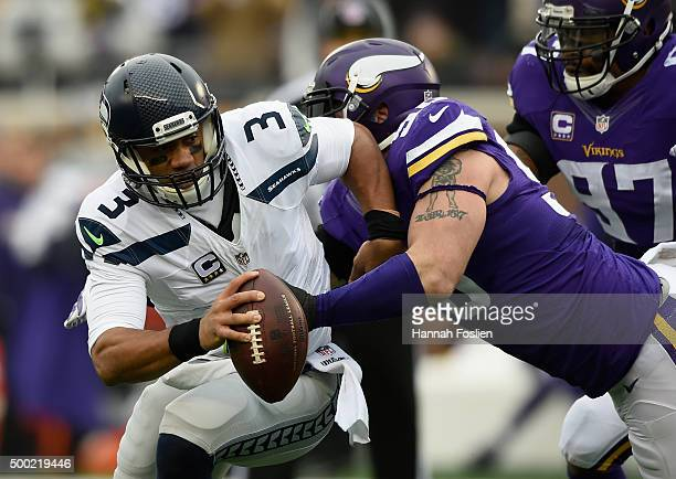 Brian Robison of the Minnesota Vikings wraps up quarterback Russell Wilson of the Seattle Seahawks during the second quarter of the game on December...