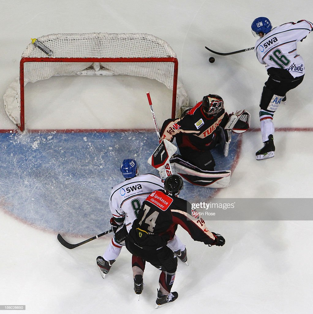 Brian Roloff (#16) of Augsburg fails to score over Dimitri Paetzold (C), goaltender of Hannover during the DEL match between Hannover Scorpions and Augsburger Panther at TUI Arena at TUI Arena on January 9, 2013 in Hanover, Germany.