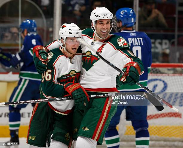 Brian Rolston of the Minnesota Wild celebrates the goal of teammate Pierre-Marc Bouchard during their game against the Vancouver Canucks at General...