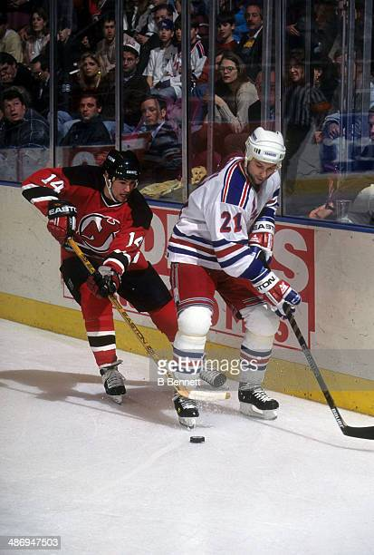 Brian Rolston of the New Jersey Devils battles with Sergei Zubov of the New York Rangers on March 8, 1995 at the Madison Square Garden in New York,...