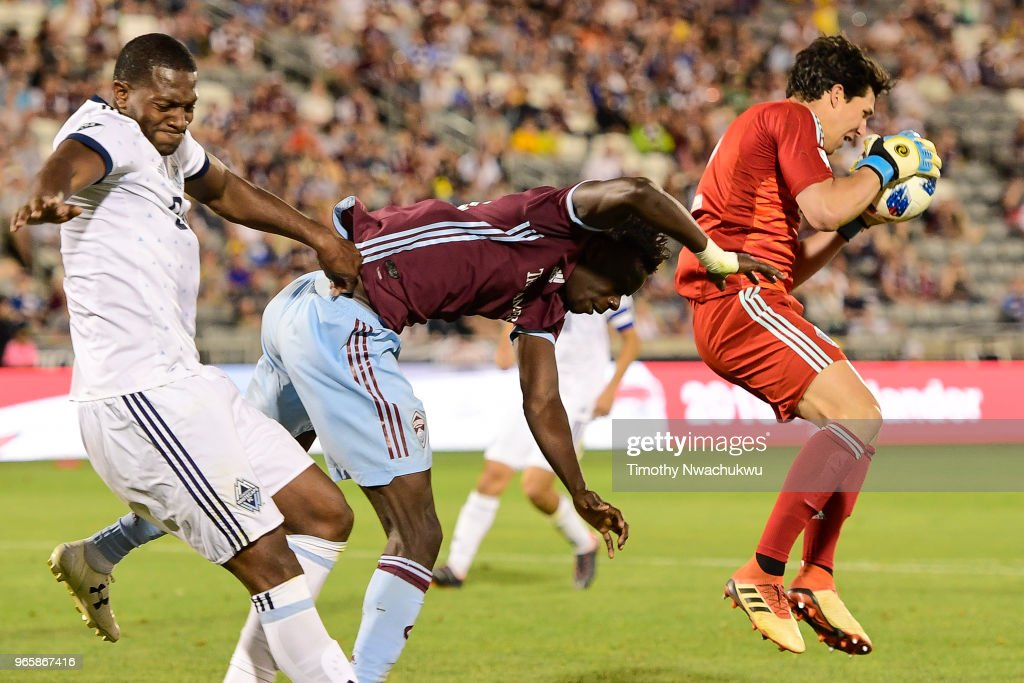 Brian Rowe #12 of Vancouver Whitecaps collects a save past Dominique Badji #14 of Colorado Rapids at Dick's Sporting Goods Park on June 1, 2018 in Commerce City, Colorado.