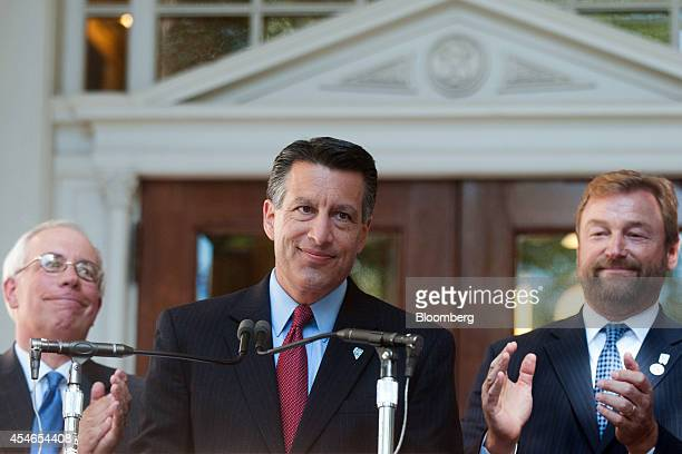 Brian Sandoval, governor of Nevada, center, is applauded by Pat Hickey, a republican member of the Nevada Assembly, left, Senator Dean Heller, a...