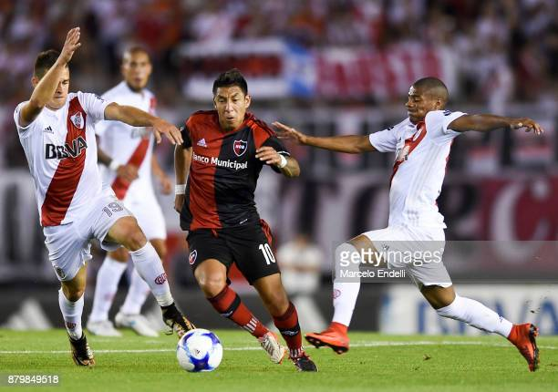 Brian Sarmiento of Newell's Old Boys fights for the ball with Rafael Santos Borre and Nicolas De La Cruz of River Plate during a match between River...