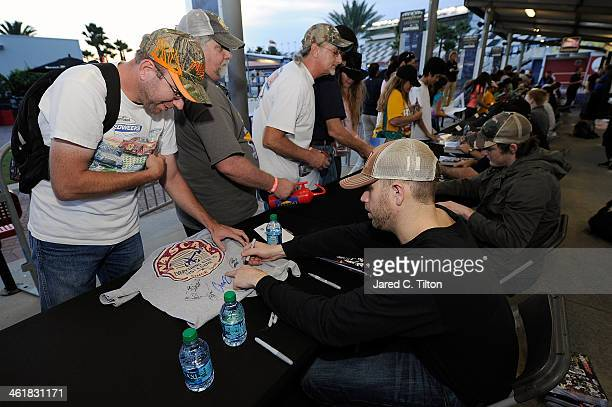 Brian Scott driver of the Shore Lodge Chevrolet signs autographs along with other Nationwide Series drivers during NASCAR Preseason Thunder at...