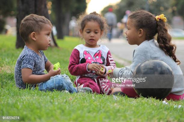 Brian Steven Tole Edilianys Rojas and Ediangelis Alexandra Rojas play outside one of a bus terminal in Bogota Colombia while their parents sell...
