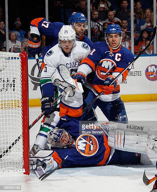 Brian Strait, John Tavares and goaltender Evgeni Nabokov of the New York Islanders combine to stop Mike Santorelli of the Vancouver Canucks during...