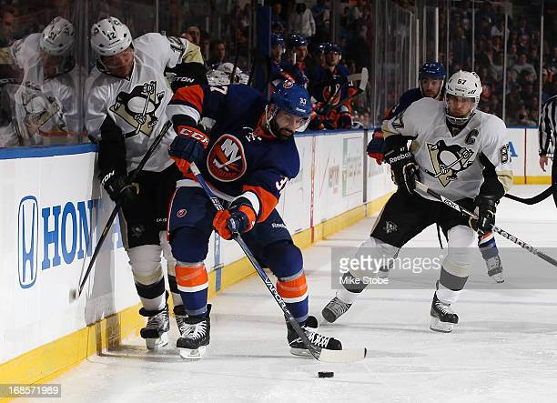 Brian Strait of the New York Islanders battles for the puck with Jarome Iginla of the Pittsburgh Penguins as Sidney Crosby of the Pittsburgh Penguins...