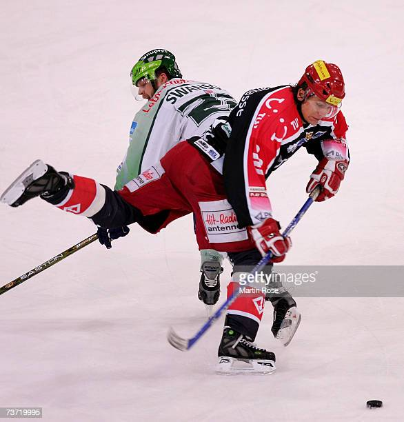 Brian Swanson of Nuremberg and Rene Roethke of Hanover fight for the puck during the DEL Bundesliga play off quarter final game between Hanover...