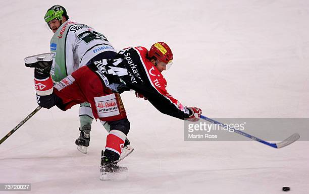 Brian Swanson of Nuremberg and Rene Roethke of Hanover fight for the puck during the DEL Bundesliga paly off quarter final game between Hanover...