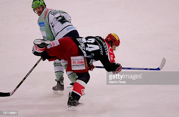 Brian Swanson of Nuremberg tackles Rene Rowthke of Hanover during the DEL Bundesliga play off quarter final game between Hanover Scorpions and...