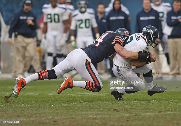 Brian Urlacher of the Chicago Bears tackles Russell Wilson of the Seattle Seahawks at Soldier Field on December 2, 2012 in Chicago, Illinois. The...