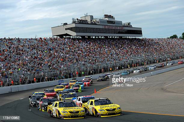 Brian Vickers driver of the Dollar General Toyota and Matt Kenseth driver of the Dollar General Toyota lead the field through turn one during the...