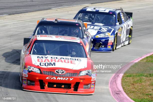 Brian Vickers driver of the MyClassicGaragecom Toyota leads Denny Hamlin driver of the FedEx Express Toyota and Jimmie Johnson driver of the Lowe's...