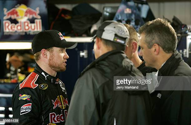 Brian Vickers driver of the Red Bull Toyota talks with members of his team in the garage area during practice for the NASCAR Sprint Cup Series...