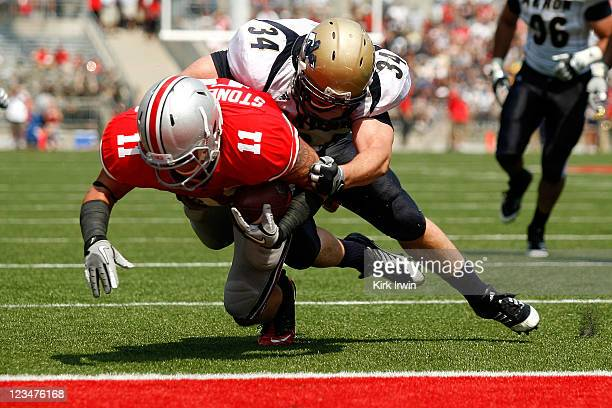 Brian Wagner of the Akron Zips is unable to stop Jake Stoneburner of the Ohio State Buckeyes as he dives into the end zone to score during the second...