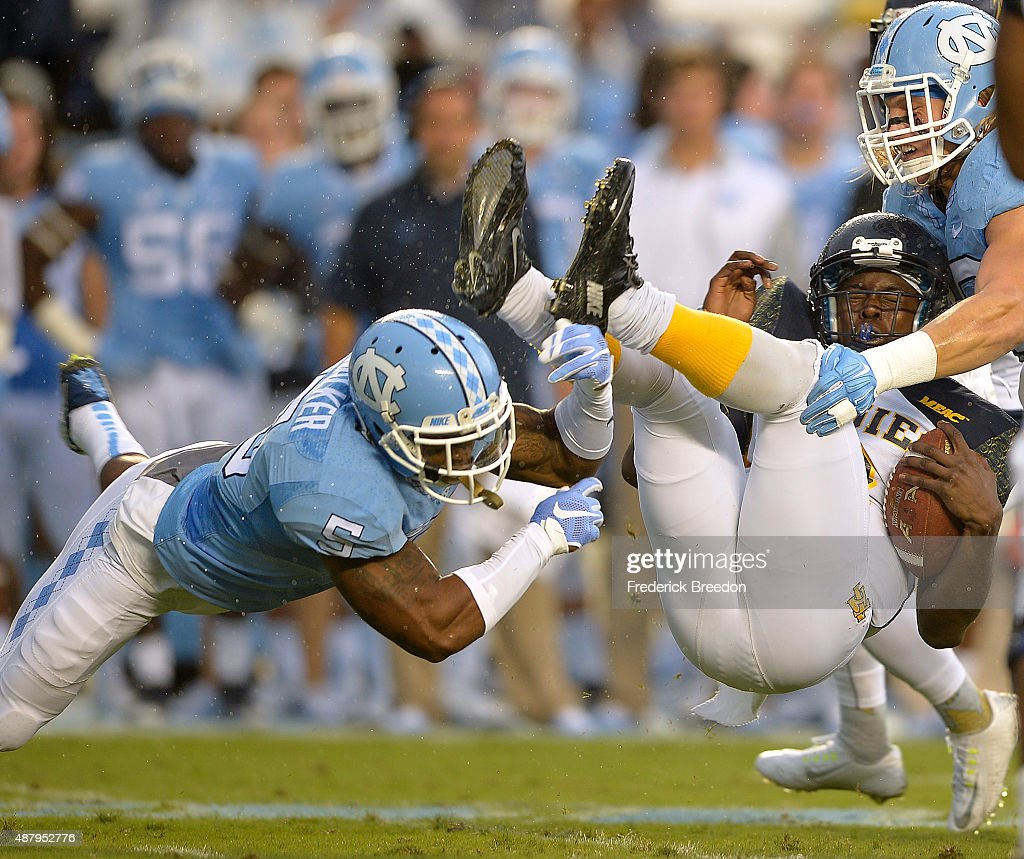 Brian Walker #5 and Jeff Schoettmer #10 of the North Carolina Tar Heels upends Kwashaun Quick #2 of the North Carolina A&T Aggies during their game at Kenan Stadium on September 12, 2015 in Chapel Hill, North Carolina.