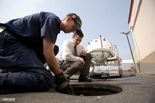 Brian Warren left and Steve Marchak of Aqua Wastewater Management pump out trap grease into a tank truck on June 1 2007 in Philadelphia Pennsylvania...