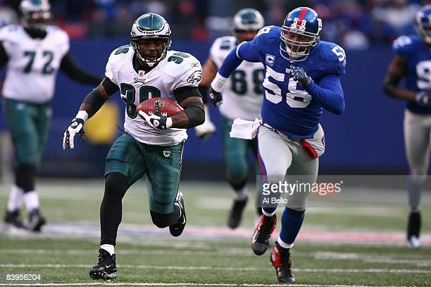 Brian Westbrook of the Philadelphia Eagles runs for a touchdown as Antonio Pierce of The New York Giants gives chase in the fourth qurter of their...