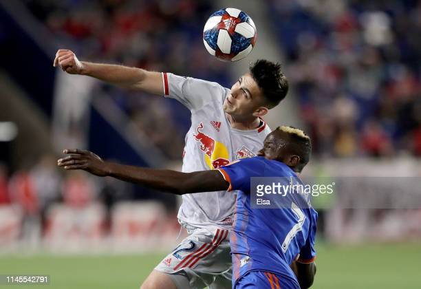 Brian White of New York Red Bulls and Roland Lamah of FC Cincinnati battle for the ball in the second half at Red Bull Arena on April 27, 2019 in...