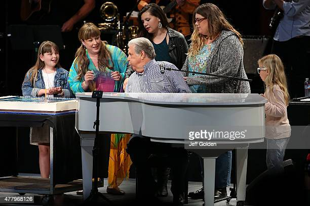 Brian Wilson blows out a birthday candle on his cake while daughter Carnie Wilson granddaughter Lola Sofia Bonfiglio and guests celebrate his 73rd...
