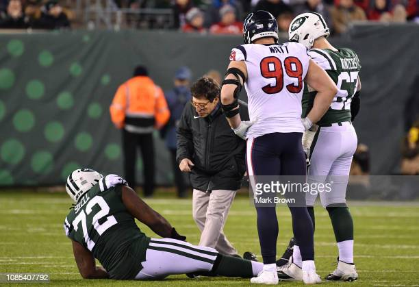 Brian Winters of the New York Jets and JJ Watt of the Houston Texans look over an injured Brandon Shell of the New York Jets at MetLife Stadium on...