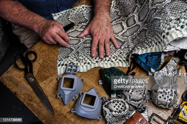 TOPSHOT Brian Wood makes snake skin face masks inside his workshop in Delray Beach some 52 Miles north of Miami on May 21 2020 A Florida craftsman...