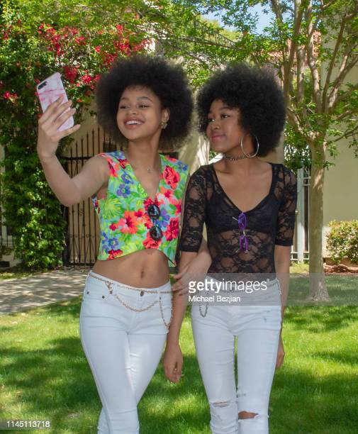 Briana Roy and Jenasha Roy wearing A Token Of necklace at Giveback Day at TAP The Artists Project on April 25 2019 in Los Angeles California