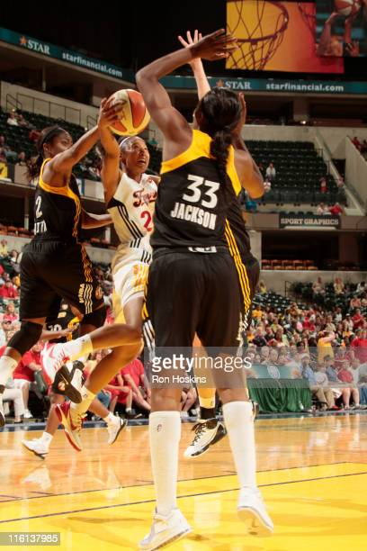 Briann January of the Indiana Fever battles Ivory Latta and Tiffany Jackson of the Tulsa Shock at Conseco Fieldhouse on June 14 2011 in Indianapolis...