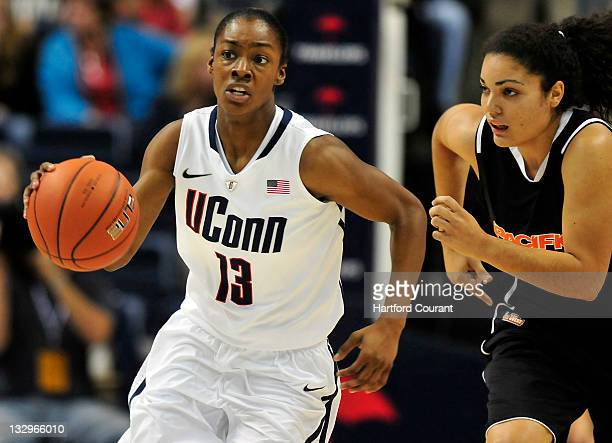 Brianna Banks of Connecticut pushes the ball up court after getting a lose ball from Brianna Johnson of Pacific at Gampel Pavilion in Storrs...