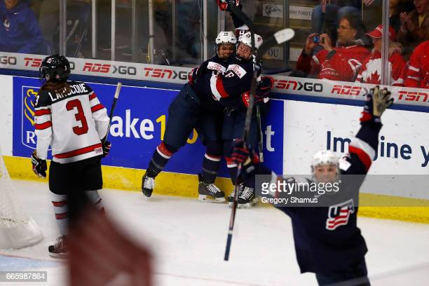 Brianna Decker and Kendall Coyne of the United States celebrate a game winning overtime goal by Hilary Knight next to Jocelyne Larocque of Canada in...