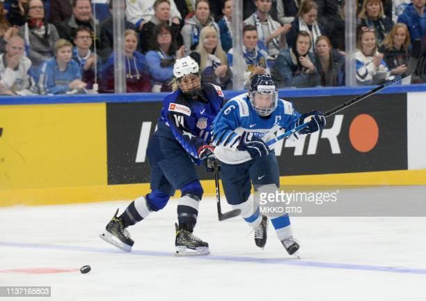 Brianna Decker of the United States and Jenni Hiirikoski of Finland vie during the IIHF Women's Ice Hockey World Championships final match between...