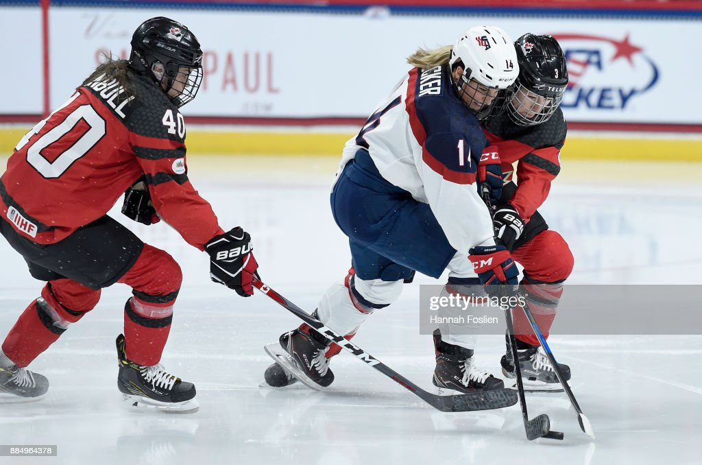 Brianna Decker #14 of the United States controls the puck against Blayre Turnbull #40 and Jocelyne Larocque #3 of Canada during the second period of the game on December 3, 2017 at Xcel Energy Center in St Paul, Minnesota. Canada defeated the United States 2-1 in overtime.