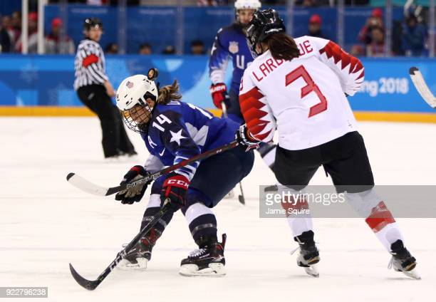 Brianna Decker of the United States controls the puck against Jocelyne Larocque of Canada in overtime during the Women's Gold Medal Game on day...