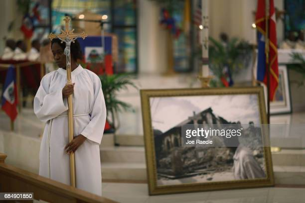 Brianna Francois carries the cross past a framed picture of a church that was destroyed by the massive 2010 Earthquake in Haiti during a service at...