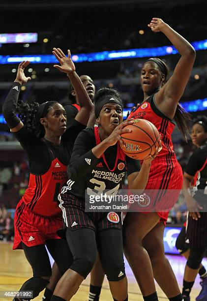 Brianna Fraser of the East team tries to get off a shot between Lashann Higgs and Kalani Brown of the West team during the 2015 McDonalds's All...