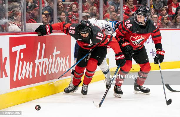 Brianne Jenner and Natalie Spooner of Canada block out Hannah Brandt of the United States while trying to recover the loose puck during game four of...