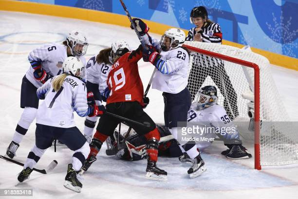 Brianne Jenner of Canada and Sidney Morin of the United States battle for the puck during the Women's Ice Hockey Preliminary Round Group A game on...